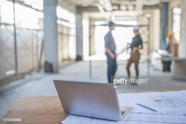 laptop op een lijst met blauwdrukken op een bouwplaats - incidental people stockfoto's en -beelden