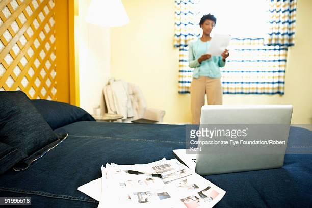 laptop on bed with woman by window in background