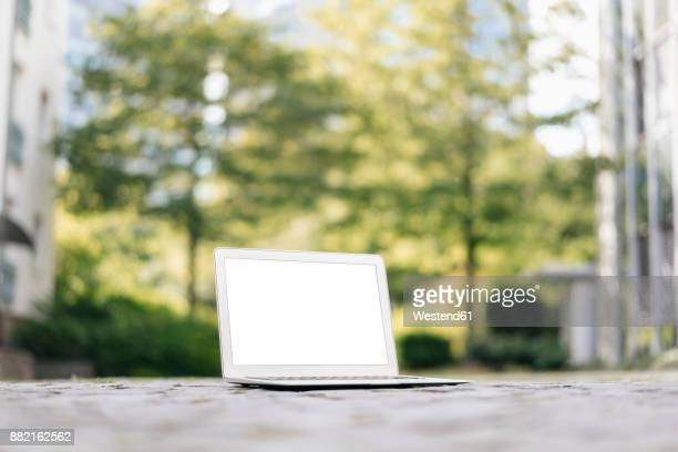 Laptop on cobblestones in park with office buildings in background