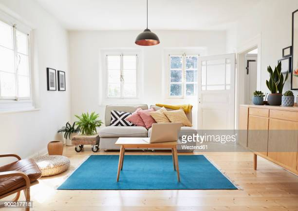 laptop on coffee table in a modern living room of an old country house - living room stock pictures, royalty-free photos & images