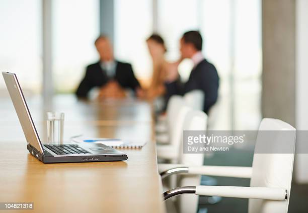 laptop on conference room table with business people in background - absence photos et images de collection
