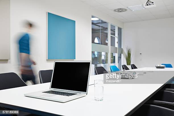 Laptop on conference table with blurred businessman in the background