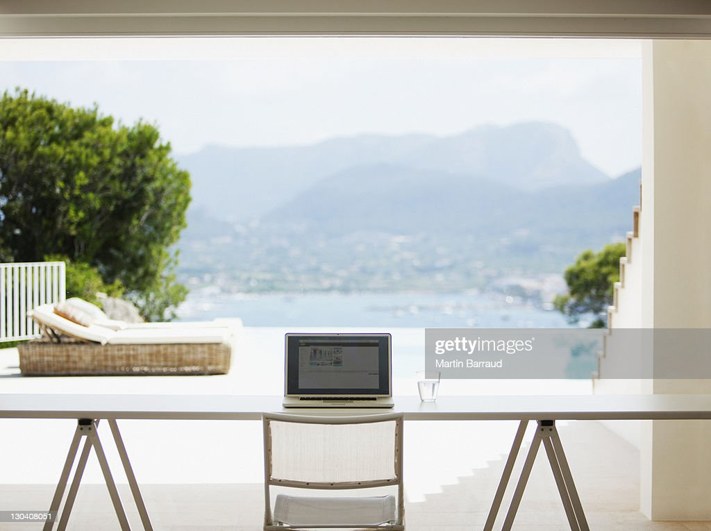 Laptop on desk in living room : Stock Photo