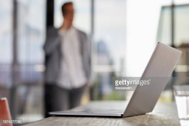 laptop on desk in office with businessman in background - focus on foreground stock pictures, royalty-free photos & images