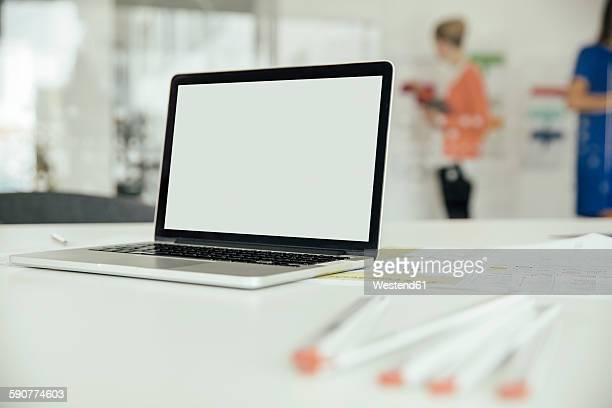 Laptop on desk in office with employees in background