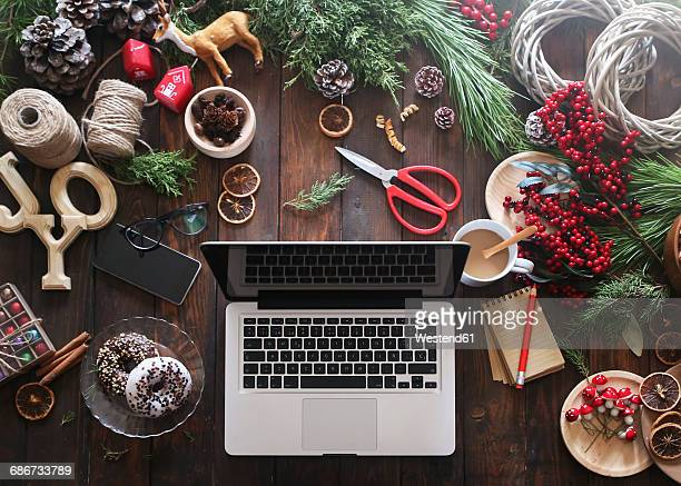 Laptop on desk with working material for Advent wreaths