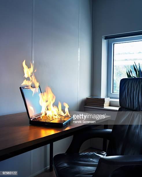 Laptop on fire at desk in office