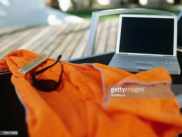 laptop on patio chair,orange shirt in foreground - オレンジ色のシャツ ストックフォトと画像