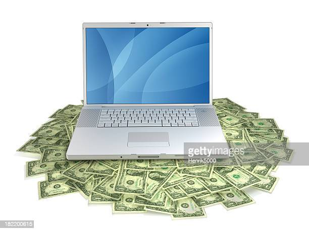 Laptop on pile of dollars, with clipping path