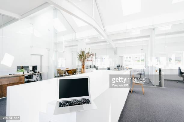 Laptop on railing in office