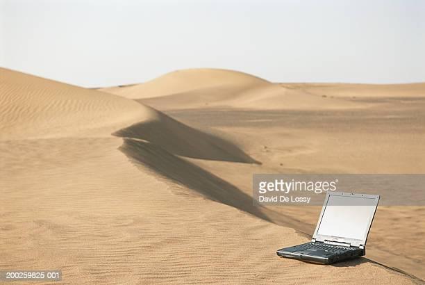 Laptop on sand in desert
