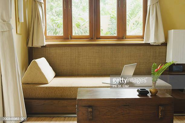 laptop on sofa beside window - tidy room stock pictures, royalty-free photos & images