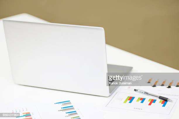 Laptop on table with income charts and graphs