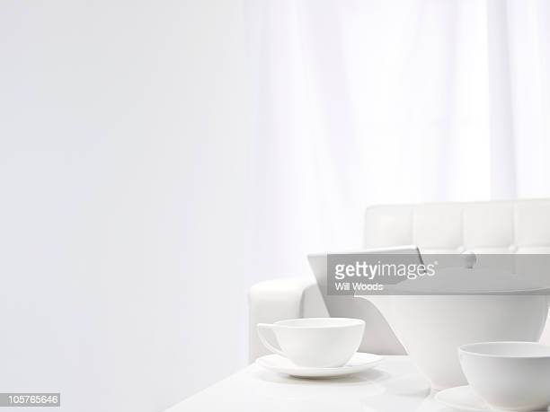 Laptop on the sofa along white tea set in a white