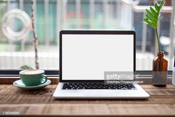 laptop on the table with coffee shop background. save path. - unbeschrieben stock-fotos und bilder