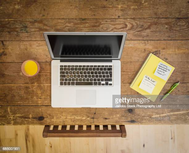 laptop, orange juice and notebook on wooden table