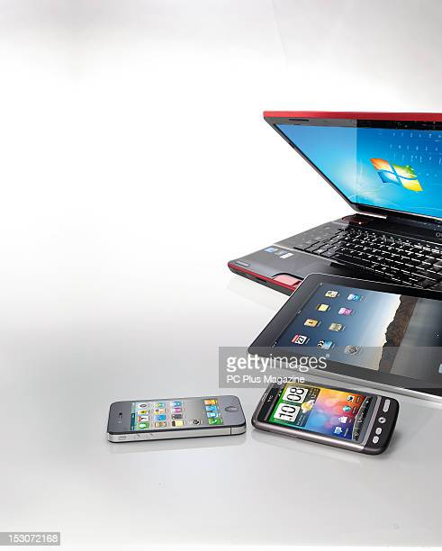 A laptop PC tablet Android smartphone and Apple iPhone on white taken on October 15 2010