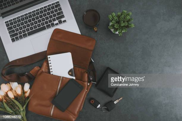laptop, satchel leather bag, mobile phone and personal belongings on dark gray background - flat lay stock pictures, royalty-free photos & images
