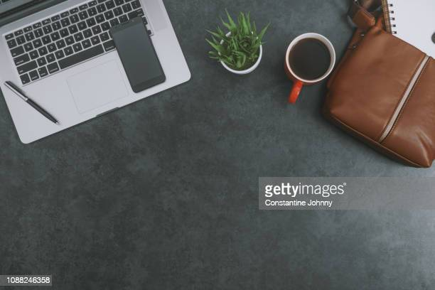 laptop, satchel leather bag, mobile phone and red coffee mug on dark gray background - gray purse stock pictures, royalty-free photos & images