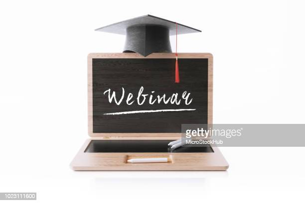 laptop shaped blackboard with a graduation cap on white background - webinar stock photos and pictures