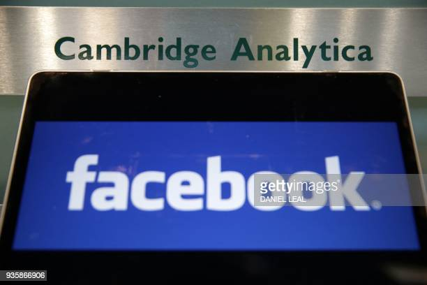 A laptop showing the Facebook logo is held alongside a Cambridge Analytica sign at the entrance to the building housing the offices of Cambridge...
