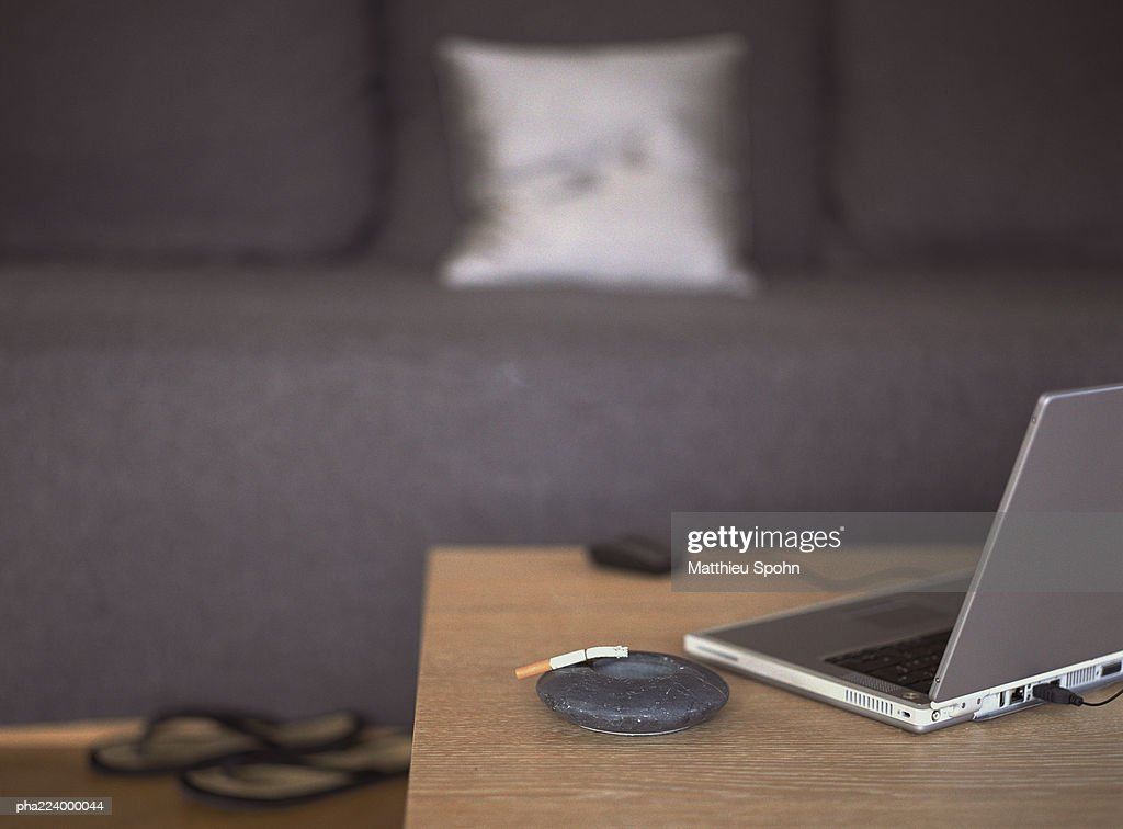 Laptop sitting on table next to ash tray in front of couch. : Stockfoto