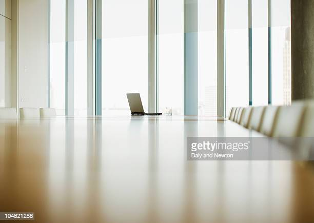 laptop sitting on table of empty conference room - focus on background stock pictures, royalty-free photos & images