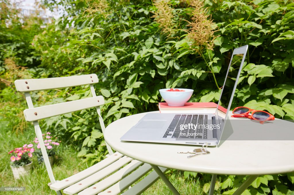 Laptop standing on table in garden : Stock Photo