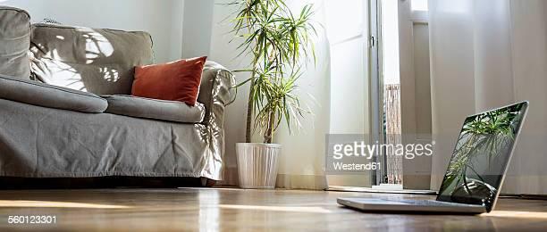 Laptop standing on wooden floor in a living room