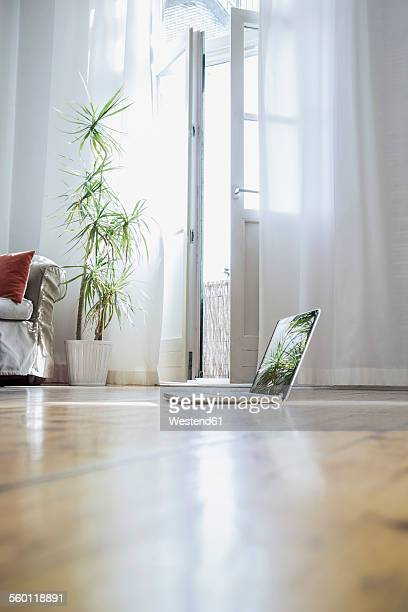 Laptop standing on wooden floor of a living room
