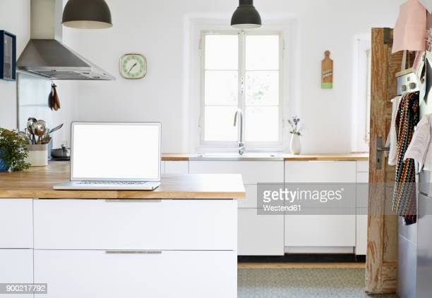 Laptop standing on worktop in a modern kitchen