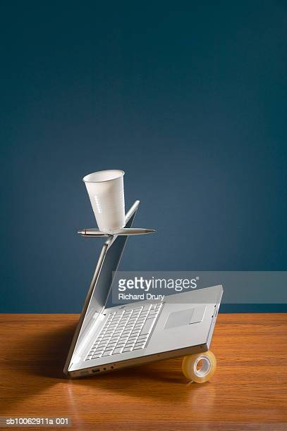 Laptop, sticky tape, pen and plastic cup balanced together on desk