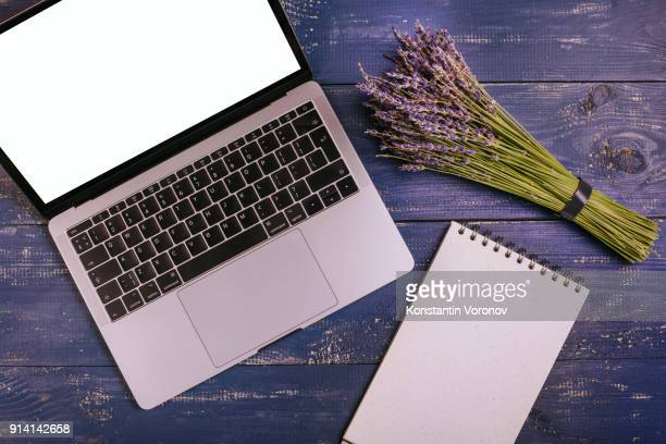 A laptop with a blank screen is on a blue table next to a bouquet of lavender. Next to it is a blank notebook with kraft paper. Top view