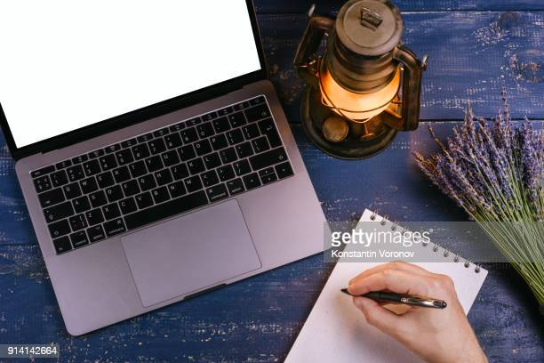 A laptop with a blank screen is on a blue table next to a bouquet of lavender and kerosene lamp. Next to it is a blank notebook with kraft paper. Over the notepad the man's hand holds the pen. Top view