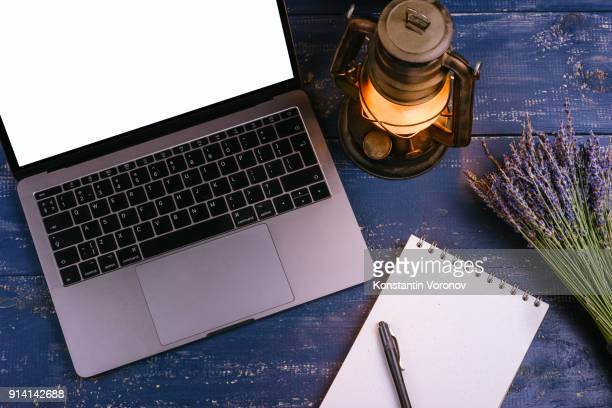 A laptop with a blank screen is on a blue table next to a bouquet of lavender and kerosene lamp. Next to it is a blank notebook with kraft paper and a pen. Top view