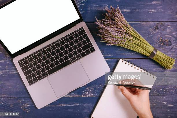 A laptop with a blank screen is on a blue table next to a bouquet of lavender. Next to it is a blank notebook with kraft paper. Over the notepad the man's hand holds the pen. Top view