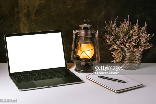 A laptop with a blank screen is on a white table next to a kerosene lamp, a room flower and a notebook with a pen. Dark textured wall on the background