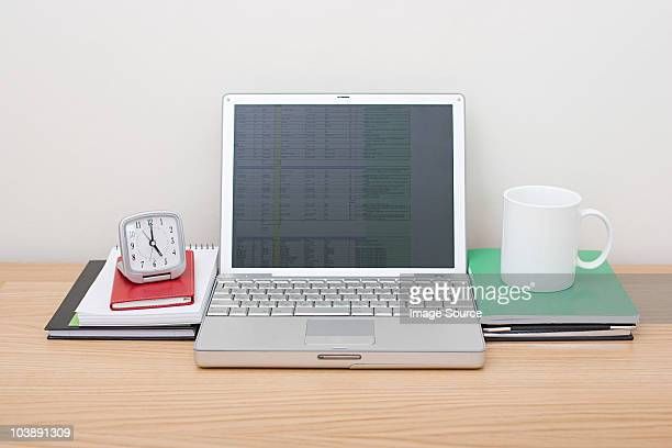 Laptop with alarm clock and mug
