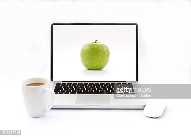 Laptop With Apple On Screen In Front Of Coffee Cup Against White Background