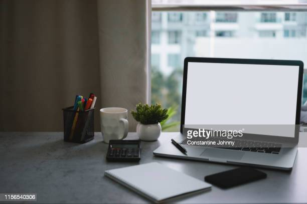 laptop with blank white screen and office supply items on word desk - iphone mockup stock pictures, royalty-free photos & images