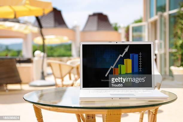 Laptop with graph on the screen at coffee shop patio