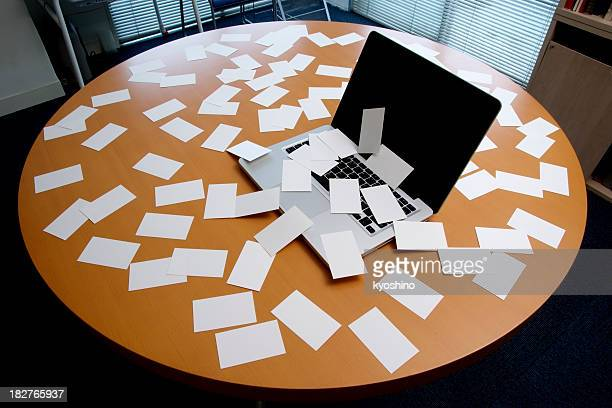 Laptop with messy blank business card on office desk