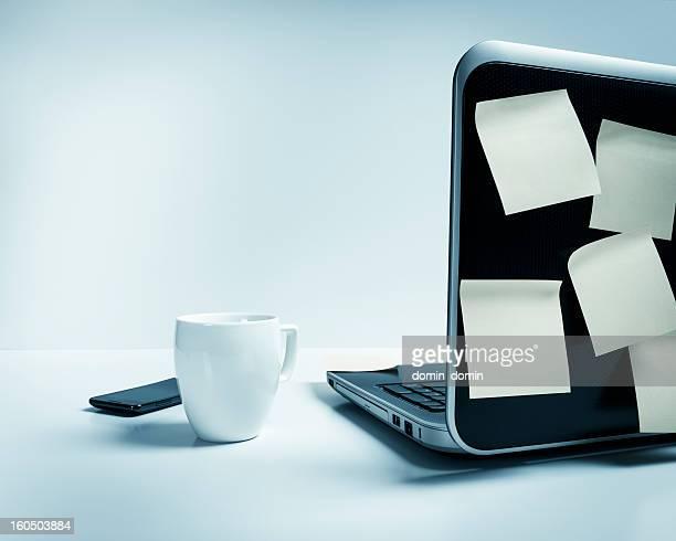 Laptop with mug, smart phone, post-it urgent notes on desk