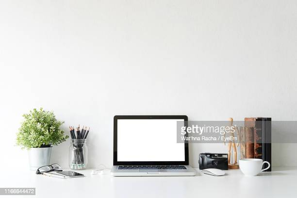 laptop with office supply on desk against gray background - 服飾品 ストックフォトと画像