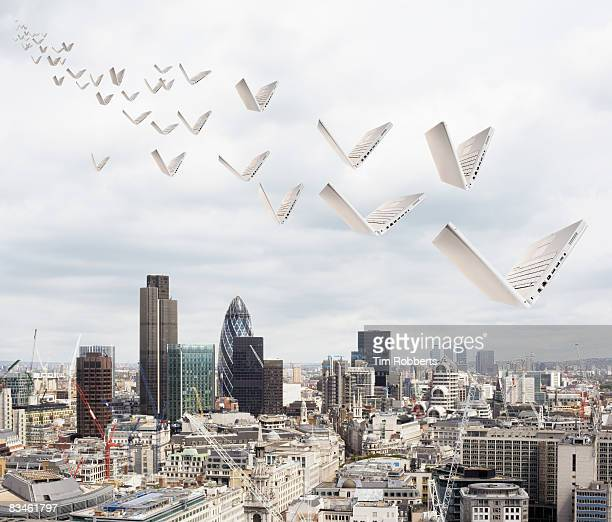 laptops flying above the city of london - flying stock pictures, royalty-free photos & images