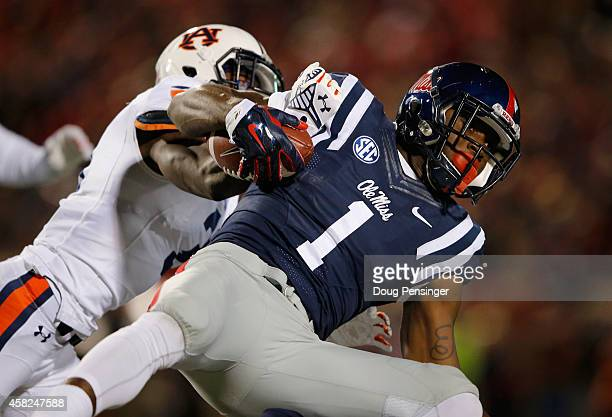 Laquon Treadwell of the Mississippi Rebels makes a first down pass reception and is tackled by Johnathan Ford of the Auburn Tigers at...