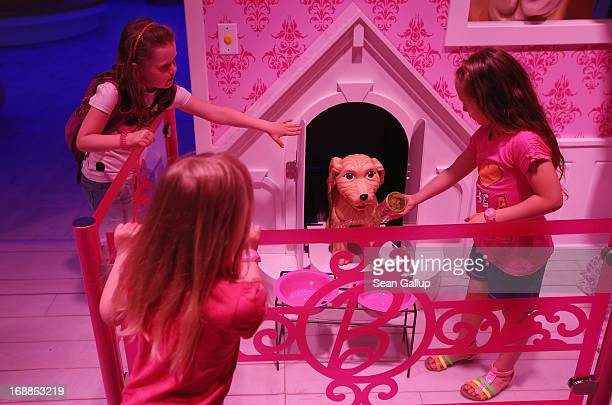 Lara Josi and Luna all 6 pet a plastic dog that emerged from his doghouse at the Barbie Dreamhouse Experience on May 16 2013 in Berlin Germany The...