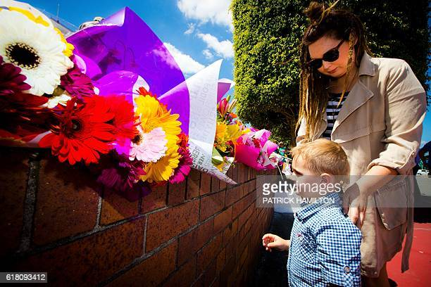 Lara Vincent and her threeyearold son Xavier lay flowers at a makeshift floral tribute at the Dreamworld theme park on the Gold Coast on October 26 a...