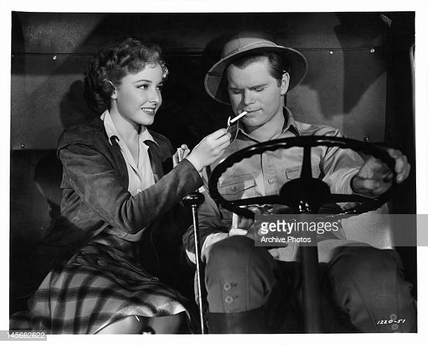 Laraine Day lights Barry Nelson's cigarette in a scene from the film 'A Yank On The Burma Road', 1942.