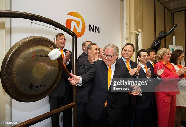 Lard Friese chief executive officer of NN Group NV center rings the opening gong at the launch of the NN Group's IPO at the Euronext Exchange in...